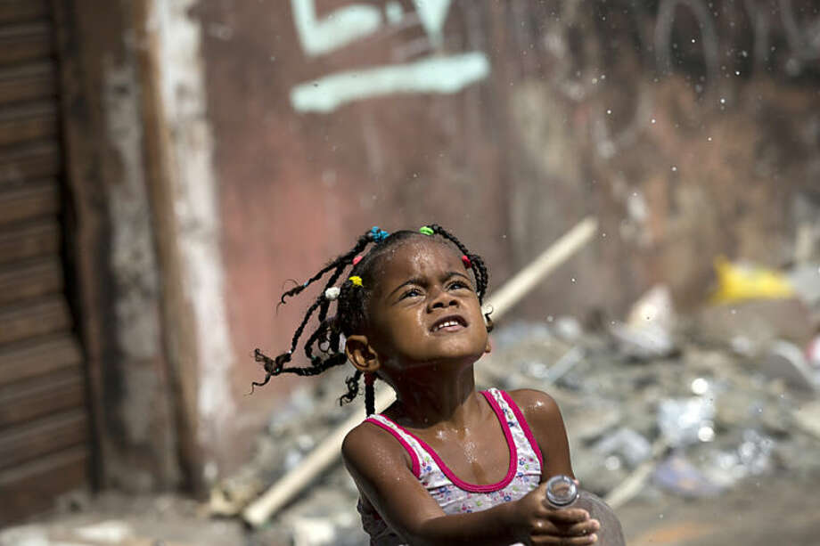 A girl throws water into the air as she plays in an area recently occupied by squatters in Rio de Janeiro, Brazil, Wednesday, April 9, 2014.Thousands of people have laid claim to a compound of abandoned office buildings owned by the private telecommunications company Oi, and named their settlement after the state-owned telecommunications Telerj. Authorities are negotiating with squatters to leave peacefully from the area they have occupied for more than a week. (AP Photo/Silvia Izquierdo)