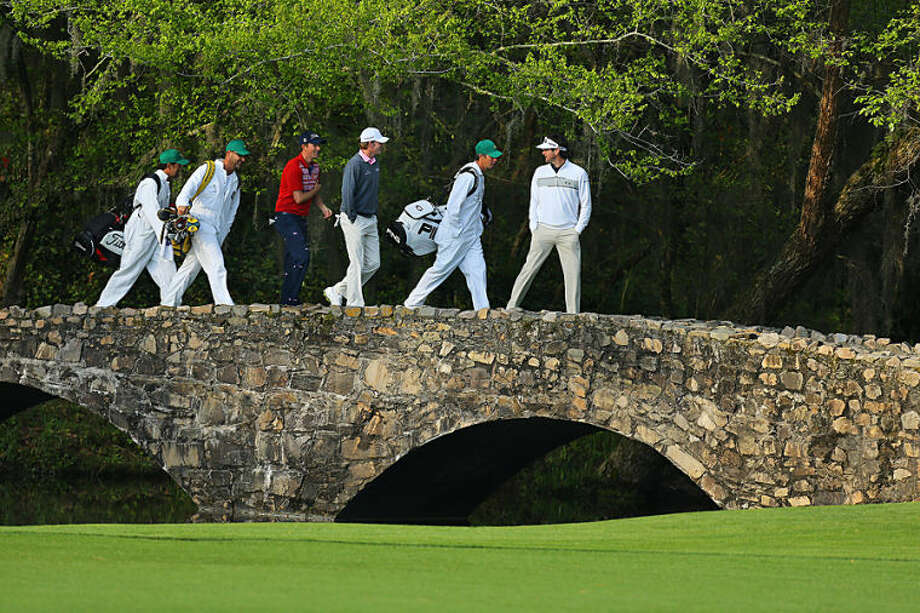 Golfers Webb Simpson, third from left, Brandt Snedeker, third from right, Bubba Watson, right, and their caddies cross the Byron Nelson Bridge after teeing off on the 13th hole during a practice round for the Masters golf tournament, Wednesday, April 9, 2014 in Augusta, Ga. (AP Photo/Atlanta Journal-Constitution, Curtis Compton) MARIETTA DAILY OUT; GWINNETT DAILY POST OUT; LOCAL TV OUT; WXIA-TV OUT; WGCL-TV OUT