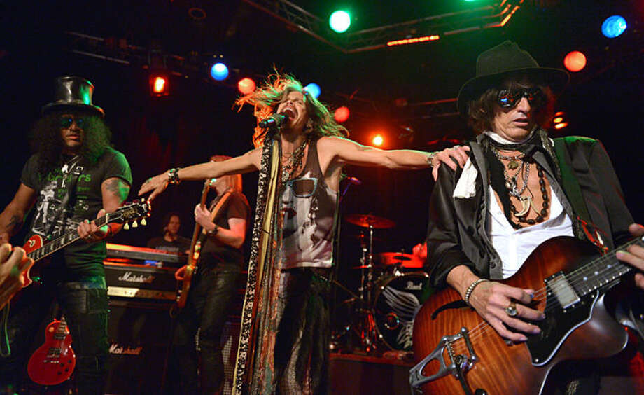 """Slash, left, performs with Steven Tyler, center, and Joe Perry, of Aerosmith, at the Whisky A Go Go on Tuesday, April 8, 2014, in Los Angeles. Aerosmith announced their """"Let Rock Rule"""" summer tour featuring Slash. (Photo by John Shearer/Invision/AP)"""