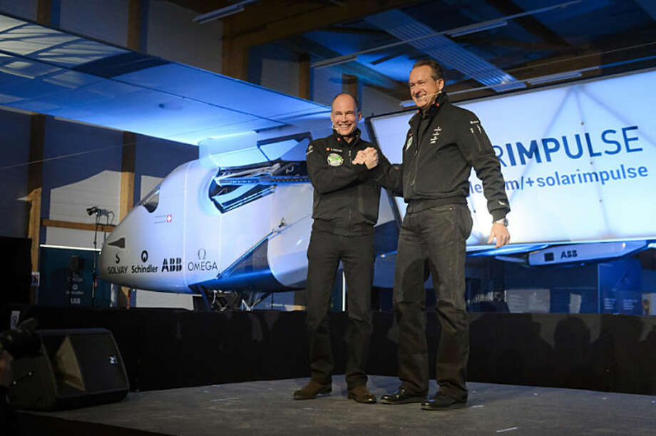 """Solar Impulse's CEO and pilot Andre Borschberg, right, and Solar Impulse's founder, chairman and pilot Bertrand Piccard, left, shake hands in front of the new experimental aircraft """"Solar Impulse 2"""", during the official presentation at the airbase in Payerne, Switzerland, Wednesday, April 9, 2014. The aircraft is the second solar plane of the Solar Impulse project. The Swiss team is planning to complete the first round-the-world solar flight next year with this plane, which they say could remain in the air indefinitely. (AP Photo/Keystone, Laurent Gillieron)"""