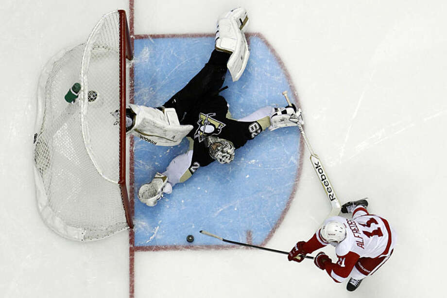 Pittsburgh Penguins goalie Marc-Andre Fleury (29) goes on his back to make the save on a shot by Detroit Red Wings' Daniel Alfredsson (11) during the shootout in an NHL hockey game in Pittsburgh, Wednesday, April 9, 2014. The Penguins won 4-3. (AP Photo/Gene J. Puskar)