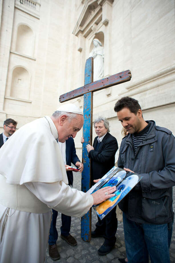 In this photo released by Vatican paper L'Osservatore Romano, Pope Francis touches an artwork next to a cross made with wood taken from immigrant's boats which landed in the Southern Italian island of Lampedusa, prior to entering St. Peter square for his weekly general audience, at the Vatican Wednesday, April 9, 2014. (AP Photo/L'Osservatore Romano)