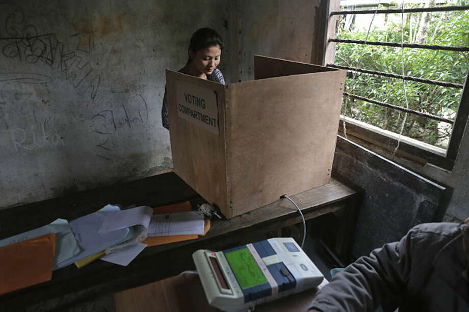 An Indian girl casts her vote at a voting center in Kalapahar, Manipur state, India, Wednesday, April 9, 2014. Hundreds of thousands of people in long-winding lines voted Wednesday in the insurgency-wracked remote northeast of India in the second phase of the county's national elections. The multiphase voting across the country runs until May 12, with results for the 543-seat lower house of parliament announced May 16. (AP Photo/Anupam Nath)