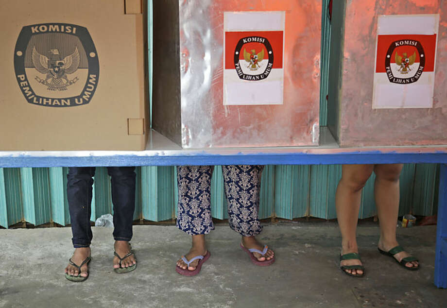 Indonesians vote in booths during the parliamentary election at a polling station in Jakarta, Indonesia, Wednesday, April 9, 2014. Polls opened Wednesday for around 187 million Indonesians eligible to vote in single-day legislative elections, a huge feat in the still-young democracy that's expected to help clear the path for the country's next president.(AP Photo/Dita Alangkara)