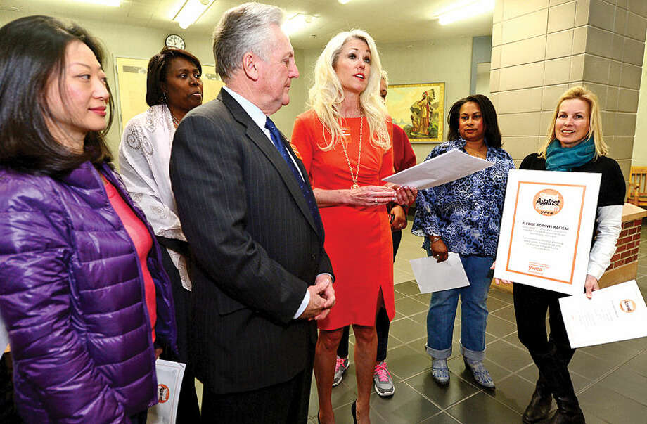 Hour photo / Erik Trautmann Norwalk Mayor Harry Rilling joins YWCA of Darien and Norwalk Executive Director Heather Cavanagh, in reading a pledge against racsim during an event, Stand Against Racism, at Norwalk City Hall Friday morning.