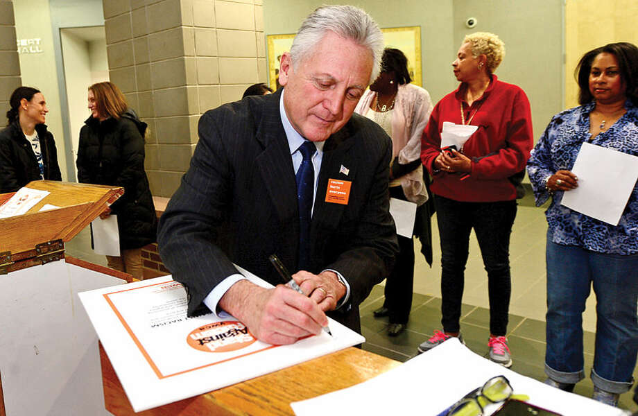 Hour photo / Erik Trautmann Norwalk Mayor Harry Rilling signs a pledge against racsim during the YWCA of Darien and Norwalk event, Stand Against Racism, at Norwalk City Hall Friday morning.