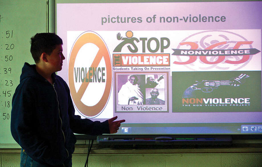"Hour photo / Erik Trautmann West Rocks Middle School student Andrew Romaniello speaks about his pictures of non-violence project during the program titled ""Safe, Peaceful and Non-Violent West Rocks Community"" Friday morning. The program is a part of Positive Behavior Intervention Supports (PBIS), a statewide program to encourage positive behavior in students."