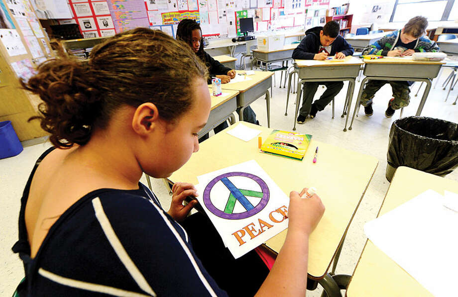 "Hour photo / Erik Trautmann West Rocks Middle School 6th grader China Tinner colors a peace sign during a program titled ""Safe, Peaceful and Non-Violent West Rocks Community"" Friday morning. The program is a part of Positive Behavior Intervention Supports (PBIS), a statewide program to encourage positive behavior in students."