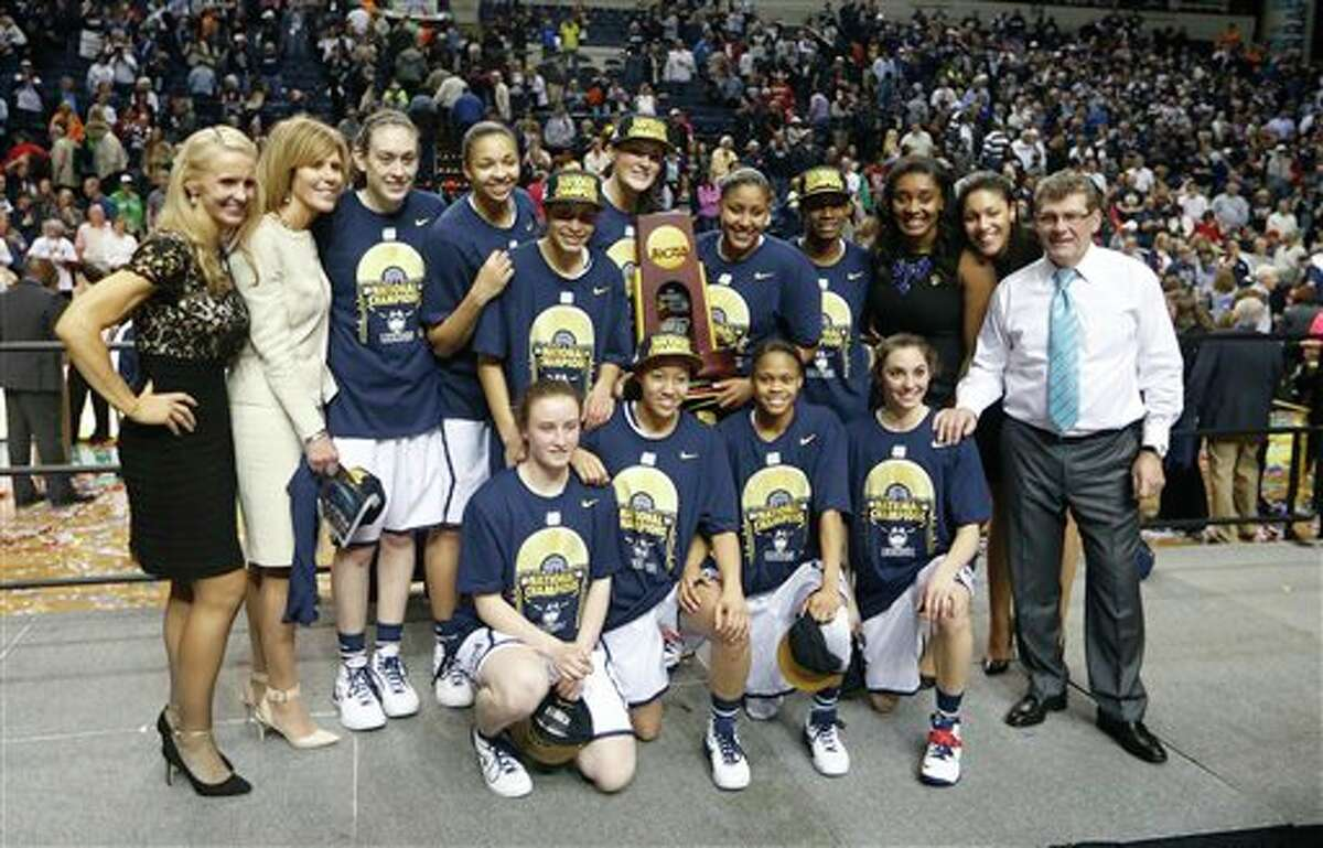 The Connecticut team poses for a photo with the trophy after the second half of the championship game against Notre Dame in the Final Four of the NCAA women's college basketball tournament, Tuesday, April 8, 2014, in Nashville, Tenn. Connecticut won 79-58. (AP Photo/John Bazemore)
