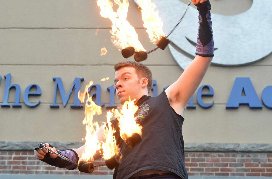 Hour Photo/Alex von Kleydorff Fire performer Maiolo Fire on the roof at the entrance to The Red Apple Gala at The Maritime Aquarium