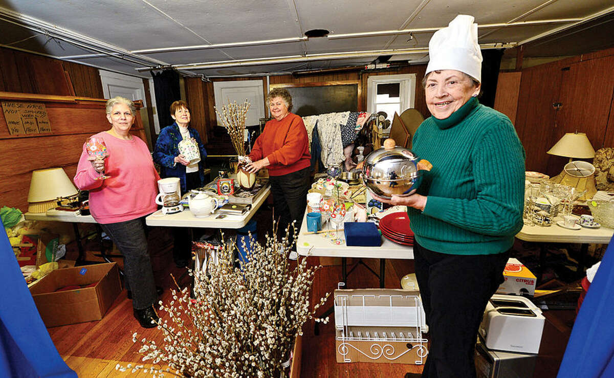 Hour photo / Erik Trautmann Christ Episcopal Church May Fair committee members, Aniat Hughes, Sarah French, Barbara Felterand Barbara Marzolf, set up for its May Fair fundraiser, set for May 2.