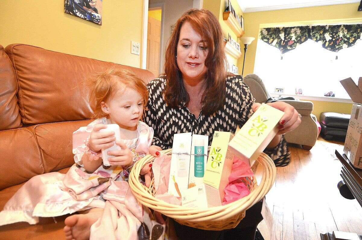 Hour Photo/Alex von Kleydorff Kristin Kreuder Overton gets help from her 2 yr old daughter Victoria, making baskets full of personal care items for distribution on Mothers day to Malta House