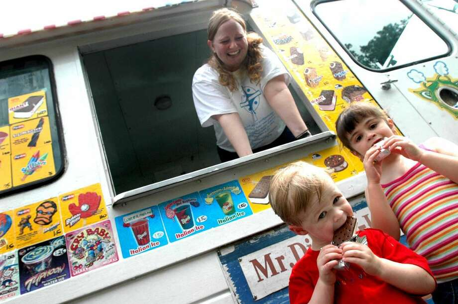 Lynn Kafer, top, enjoys the watching Nate Hussar, left, and Ellie Hussar, 4, eat ice cream that she served them from her Mr Ding-a-ling ice cream truck Tuesday, July 12, 2005, in Bethlehem, N.Y. (Steve Jacobs/Times Union archive)