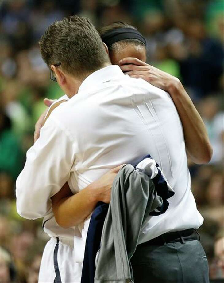 Connecticut guard Moriah Jefferson (4) embraces Connecticut head coach Geno Auriemma during the second half of the championship game against Notre Dame in the Final Four of the NCAA women's college basketball tournament, Tuesday, April 8, 2014, in Nashville, Tenn. (AP Photo/John Bazemore) / AP