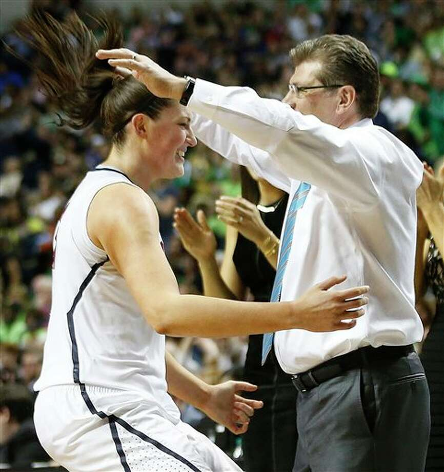 Connecticut center Stefanie Dolson (31) prepares to embrace Connecticut head coach Geno Auriemma during the second half of the championship game in the Final Four of the NCAA women's college basketball tournament, Tuesday, April 8, 2014, in Nashville, Tenn. Connecticut won 79-58. (AP Photo/John Bazemore) / AP