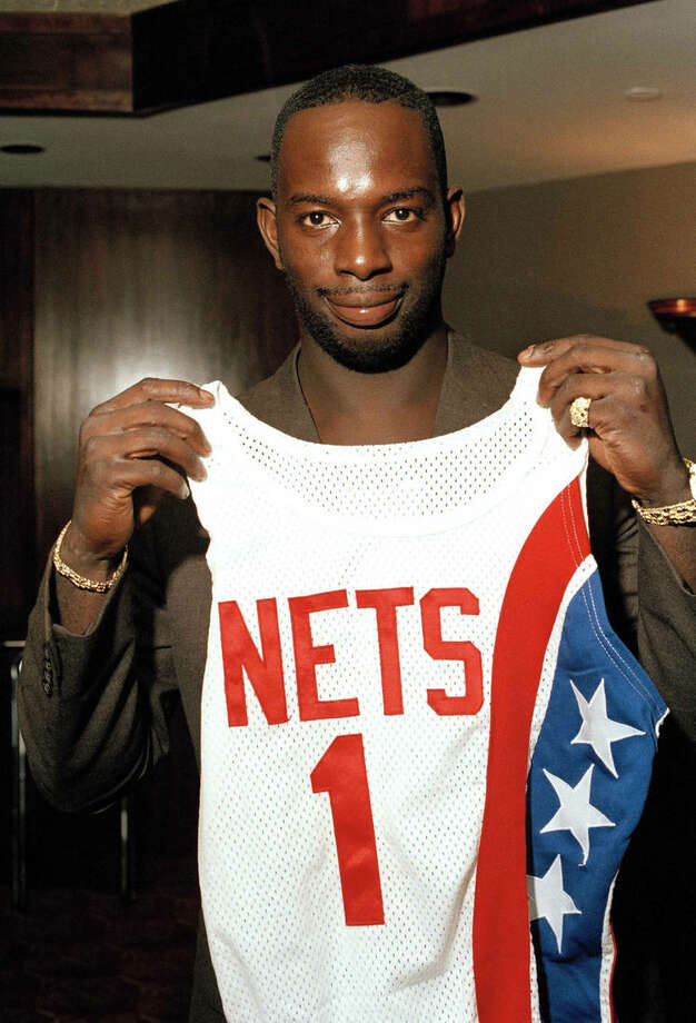 """FILE - In this Aug. 20, 1986 file photo, Dwayne """"Pearl"""" Washington, the first draft pick by the New Jersey Nets, holds up his new uniform during a press luncheon at the Meadowlands Arena in East Rutherford, N.J. Washington, who went from New York City playground wonder to Big East star for Jim Boeheim at Syracuse, has died. He was 52. Washington died Wednesday, April 20, 2015 of cancer, the university said. (AP Photo/Ron Frehm, File)"""