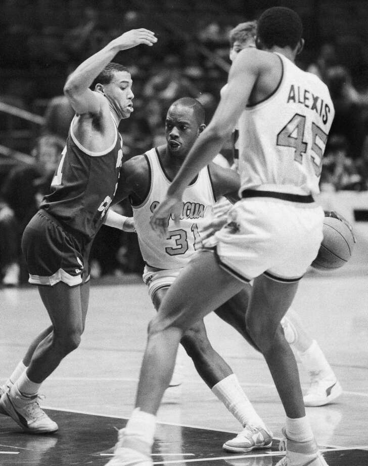 """FILE - In this March 6, 1986 file photo, Dwayne """"Pearl"""" Washington (31) of Syracuse University drives around Dana Barros (21) of Boston College during the Big East tournament at New York's Madison Square Garden. Washington, who went from New York City playground wonder to Big East star for Jim Boeheim at Syracuse, has died. He was 52. Washington died Wednesday, April 20, 2015 of cancer, the university said. (AP Photo/Richard Drew, File)"""