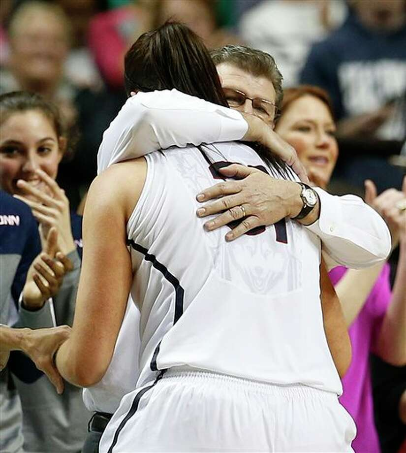 Connecticut center Stefanie Dolson (31) embraces Connecticut head coach Geno Auriemma during the second half of the championship game against Notre Dame in the Final Four of the NCAA women's college basketball tournament, Tuesday, April 8, 2014, in Nashville, Tenn. Connecticut won 79-58. (AP Photo/Mark Humphrey) / AP