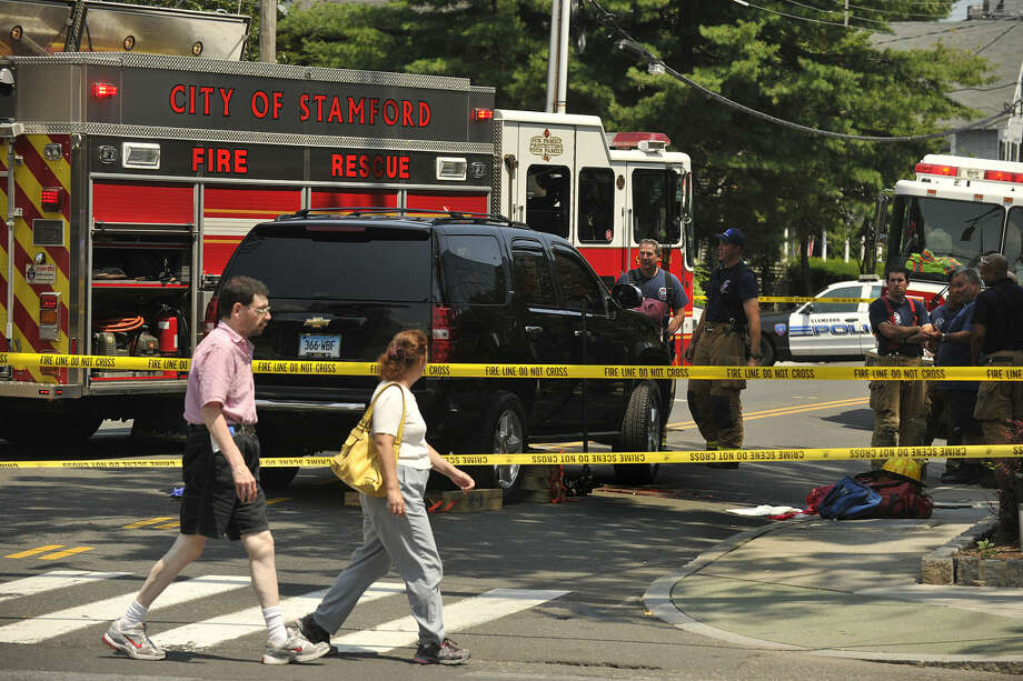 Pedestrians walk across Hoyt Street watching emergency personnel at the scene where a pedestrian was struck by a SUV at the eastern corner of Summer Street on Hoyt Street in Stamford, Conn., on Monday, July 21, 2014. Police say the pedestrian suffered life threatening injuries.(Photo: Jason Rearick)