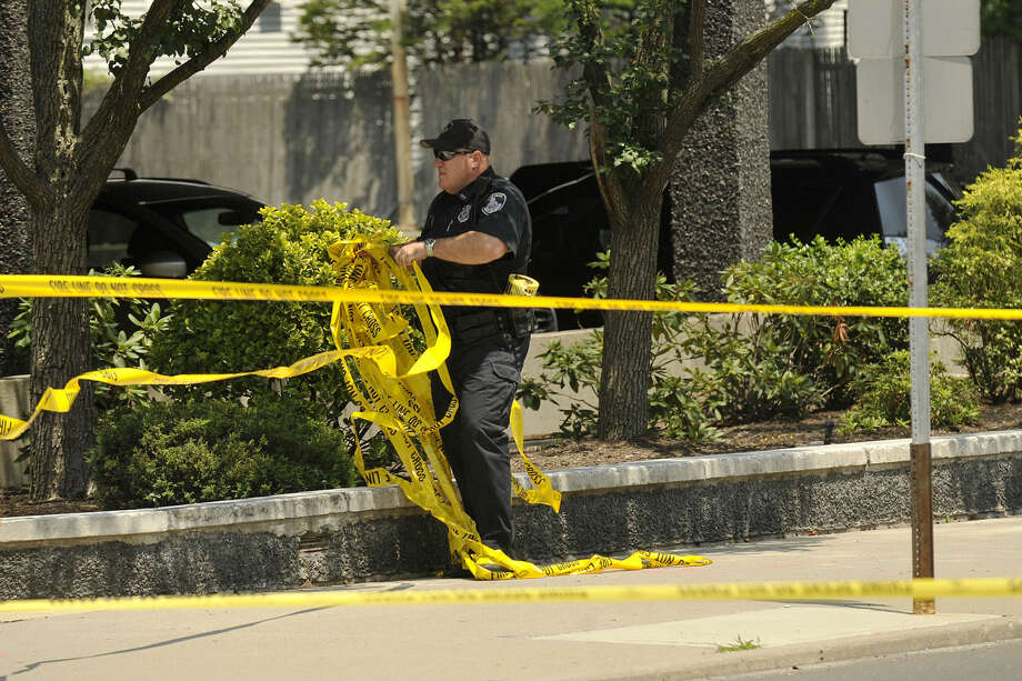 A policeman takes down caution tape at the scene where a pedestrian was struck by a SUV at the eastern corner of Summer Street on Hoyt Street in Stamford, Conn., on Monday, July 21, 2014. Police say the pedestrian suffered life threatening injuries.(Photo:Jason Rearick)