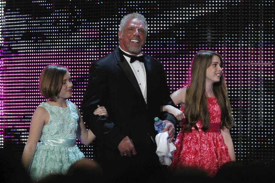 FILE - In this April 5, 2014 file photo provided by the WWE, James Hellwig, aka The Ultimate Warrior, is escorted by his daughters to the stage during the WWE Hall of Fame Induction at the Smoothie King Center in New Orleans. The WWE said Hellwig, one of pro wrestling's biggest stars in the late 1980s, died Tuesday, April 8, 2014. He was 54. (Jonathan Bachman/AP Images for WWE, File)