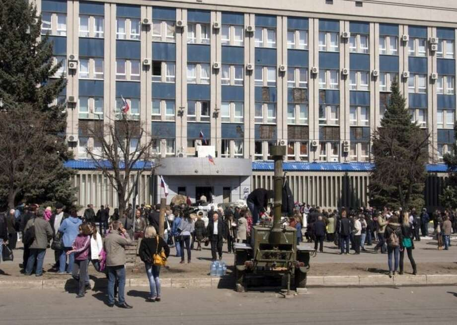 Pro-Russian activists gather in front of an entrance of the Ukrainian regional office of the Security Service in Luhansk, 30 kilometers (20 miles) west of the Russian border, in Ukraine, Tuesday, April 8, 2014. The Donetsk and Kharkiv regions and a third Russian-speaking city besieged by pro-Moscow activists over the weekend, Luhansk have a combined population of nearly 10 million out of Ukraine's 46 million, and account for the bulk of the country's industrial output. (AP Photo/Igor Golovniov)