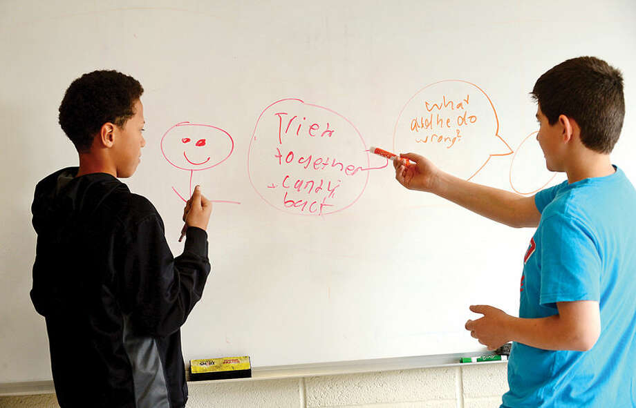 "Hour photo / Erik Trautmann West Rocks Middle School 6th graders Dontae Scullark and Daniel Didemetrio work out differneces on the white board during a program titled ""Safe, Peaceful and Non-Violent West Rocks Community"" Friday morning. The program is a part of Positive Behavior Intervention Supports (PBIS), a statewide program to encourage positive behavior in students."