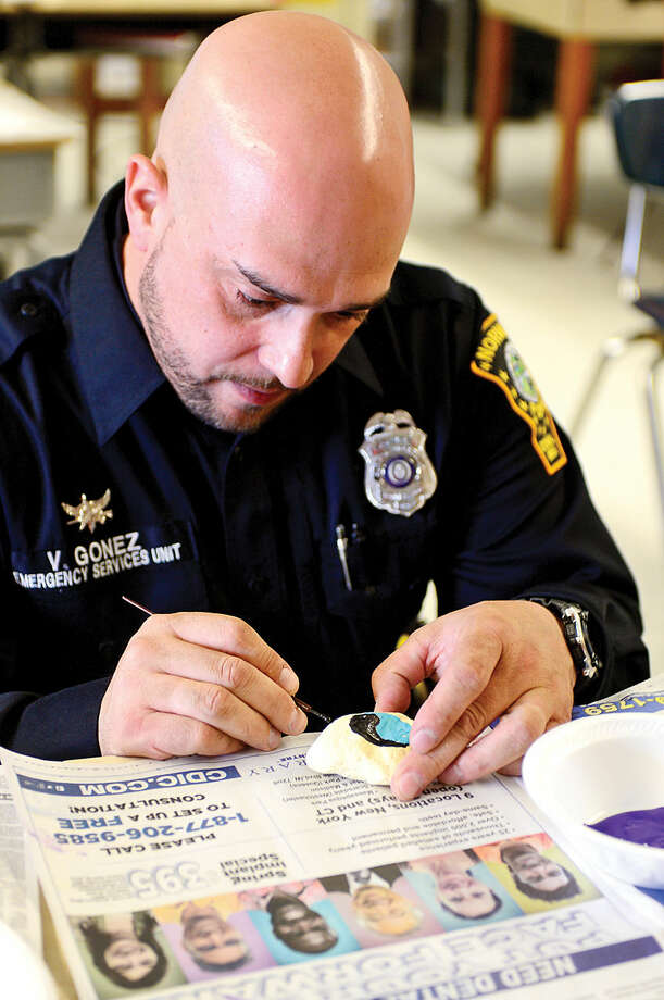 "Hour photo / Erik Trautmann Norwalk police officer Vidal Gonez paints a Peace Rock while visiting West Rocks Middle School during a program titled ""Safe, Peaceful and Non-Violent West Rocks Community"" Friday morning. The program is a part of Positive Behavior Intervention Supports (PBIS), a statewide program to encourage positive behavior in students."