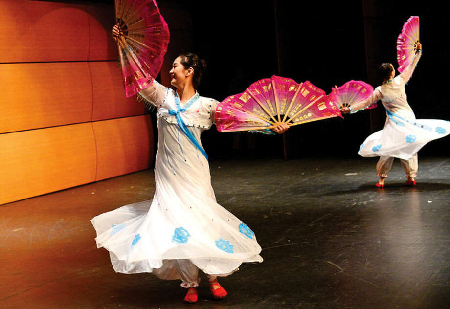 Hour photo / Erik Trautmann Members of the Dance China troupe perform wearing traditional Chinese costumes as part of Wilton High School's annual World Language and Arts Festival Wednesday. The weeklong program features several international events where students will be introduced to different cultures through language lessons, historical background and demonstrations.