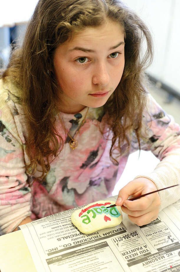 """Hour photo / Erik Trautmann West Rocks Middle School 6th grader Julia Karabin paints a Peace Rock during a program titled """"Safe, Peaceful and Non-Violent West Rocks Community"""" Friday morning. The program is a part of Positive Behavior Intervention Supports (PBIS), a statewide program to encourage positive behavior in students."""