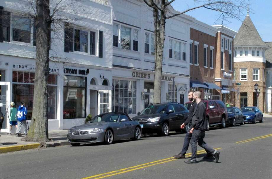 In this April 6, 2015 photo, pedestrians cross a street in downtown Darien, Conn. Local resident Christopher Stefanoni is suing the Darien Little League in federal court, saying league officials demoted his 9-year-old son to a lower-level team as retribution for his affordable housing proposal. Lawyers for the Little League deny the allegations.