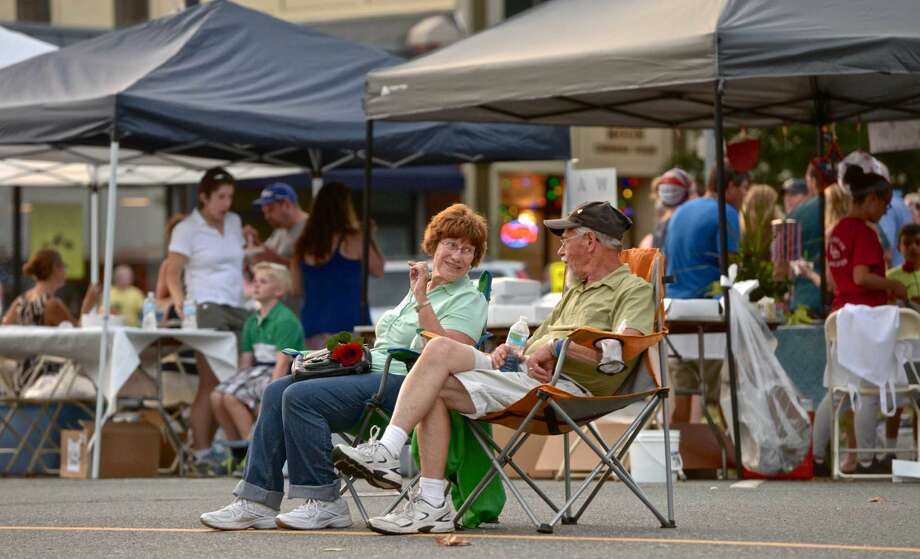 Chris and Mary Prause, of New Milford, sit in the middle of Church Street and listen to the band SongHorse 10th Annual Taste of New Milford, held on the Village Green, on Wednesday night, September 9, 2015, in New Milford, Conn.