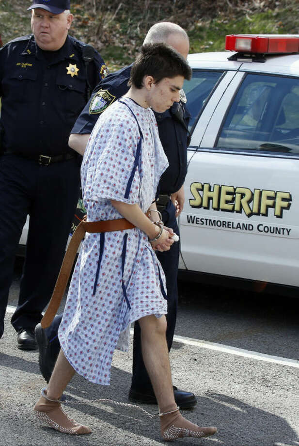 Alex Hribal, the suspect in the multiple stabbings at the Franklin Regional High School in Murrysville, Pa., is escorted by police to a district magistrate to be arraigned on Wednesday, April 9, 2014, in Export, Pa. Authorities say Hribal has been charged after allegedly stabbing and slashing 19 students and a police officer in the crowded halls of his suburban Pittsburgh high school Wednesday. (AP Photo/Keith Srakocic)