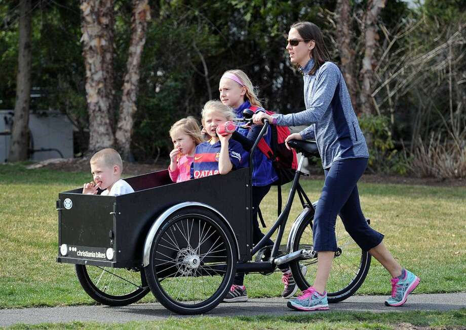 Anne Gustafsson of Old Greenwich, right, pushes her Dutch bike with her children seated in the basket, they are from left, Lars, 5, Olivia, 3, Julia, 8, as her oldest daughter Emma, 10, walks along with her on Sound Beach Avenue in Old Greenwich, Conn., Wednesday afternoon, March 23, 2016.