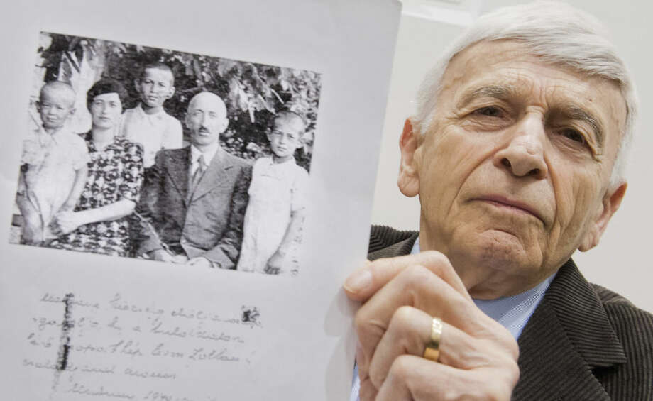 Julian Stratenschulte/Pool via APAuschwitz survivor Max Eisen shows a photograph from 1940 that shows him, center, with his parents and brothers, Thursday, April 23, in a courtroom in Lueneburg, northern Germany. Eisen attends the trial against former SS guard Oskar Groening, 93, who is accused of helping to operate the death camp Auschwitz in Nazi-occupied Poland between May and June 1944, when some 425,000 Jews from Hungary were brought there and at least 300,000 were almost immediately gassed to death.