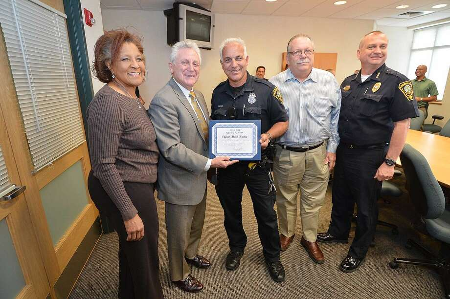Hour photo/Alex von KleydorffNorwalk Police Commissioners Fran Collier-Clemmons, Mayor Harry Rilling, Officer of the Month Mark Kucky, Charles Yost and Police Chief Thomas Kulhawik during the ceremony at Norwalk Police HQ Wednesday.