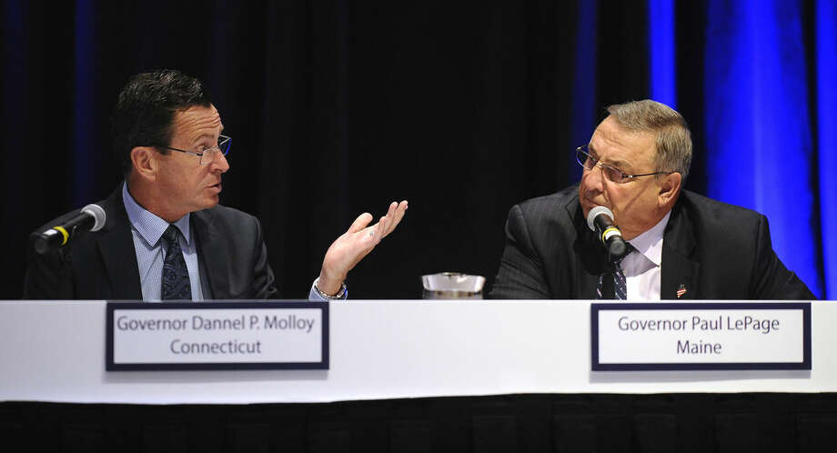 Connecticut Gov. Dannel P. Malloy, left, talks with Maine Gov. Paul LePage during a panel meeting, Thursday, April 23, 2015, in Hartford, Conn. New England's governors met Thursday to update their long-term energy strategy that increasingly relies on natural gas and efforts to build more pipelines. (AP Photo/Jessica Hill)