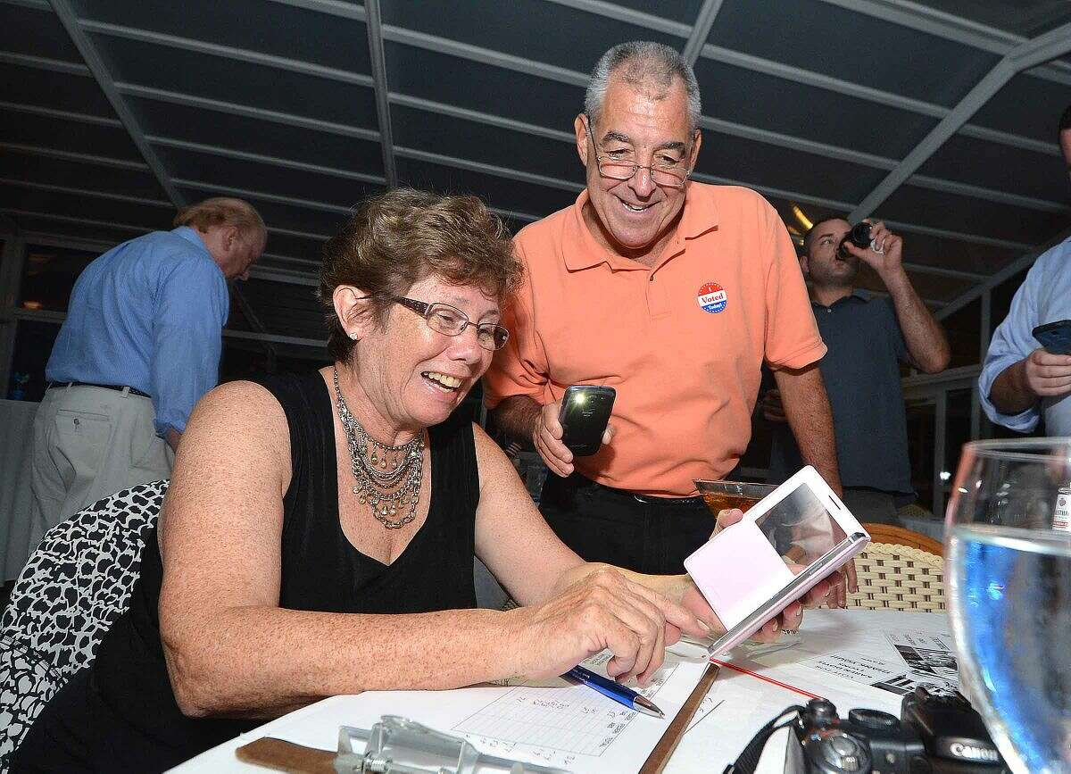 Hour Photo/Alex von Kleydorff Karen Doyle-Lyons smiles as numbers come in with help from Lou DePanfilis and his smart phone flashlight at The Norwalk Inn.