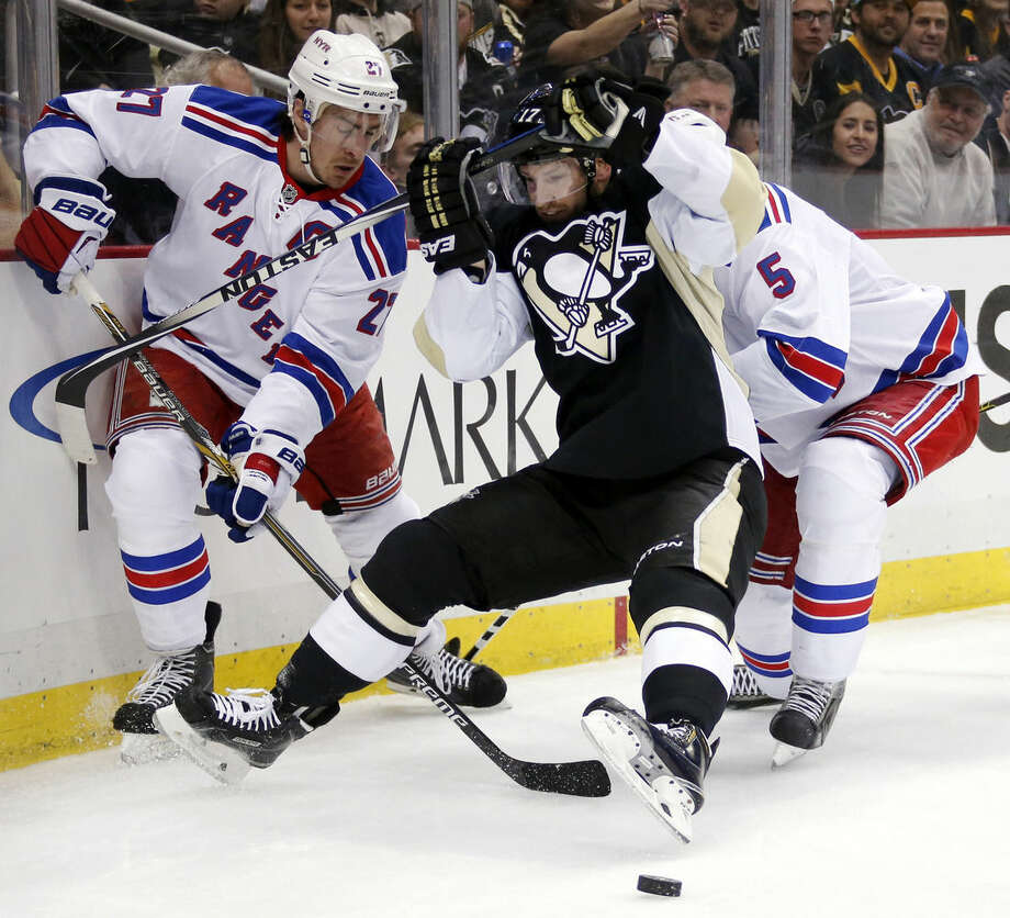 Pittsburgh Penguins' Blake Comeau (17) is checked between New York Rangers' Dan Girardi (5) and Ryan McDonagh (27) during the second period of a first-round NHL playoff hockey game in Pittsburgh on Wednesday, April 22, 2015. (AP Photo/Gene J. Puskar)