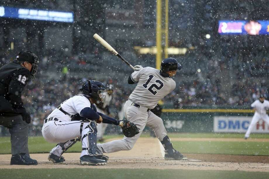 New York Yankees' Chase Headley hits a two-run single as snow falls during the first inning of a baseball game against the Detroit Tigers, Wednesday, April 22, 2015, in Detroit. (AP Photo/Carlos Osorio)