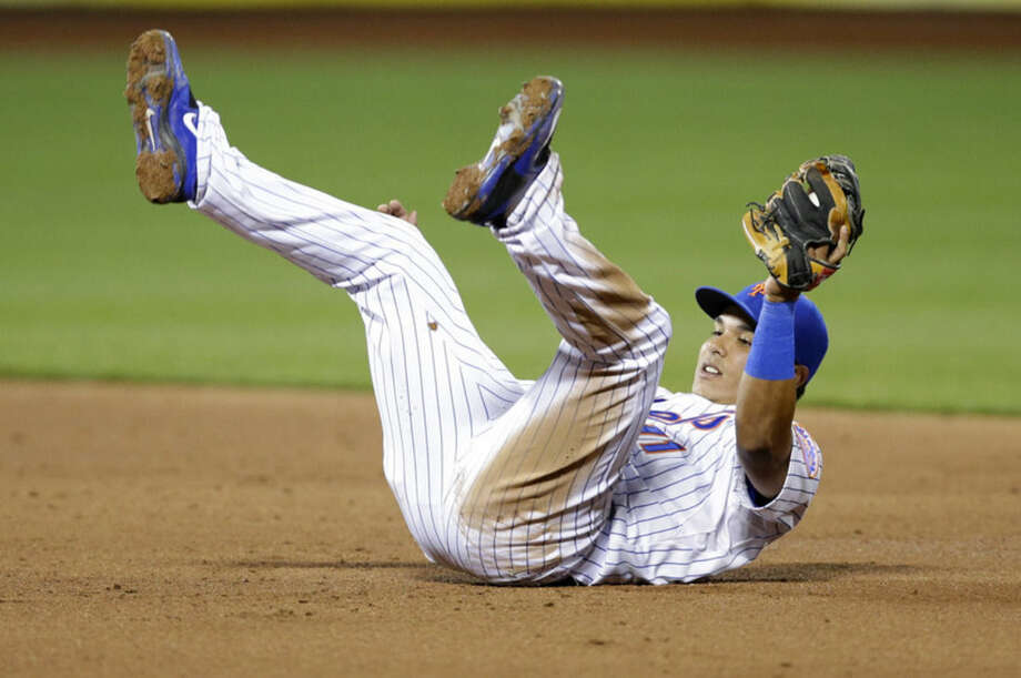 New York Mets shortstop Ruben Tejada (11) lands after leaping to catch Nick Markakis's third-inning line out in a baseball game in New York, Wednesday, April 22, 2015. (AP Photo/Kathy Willens)