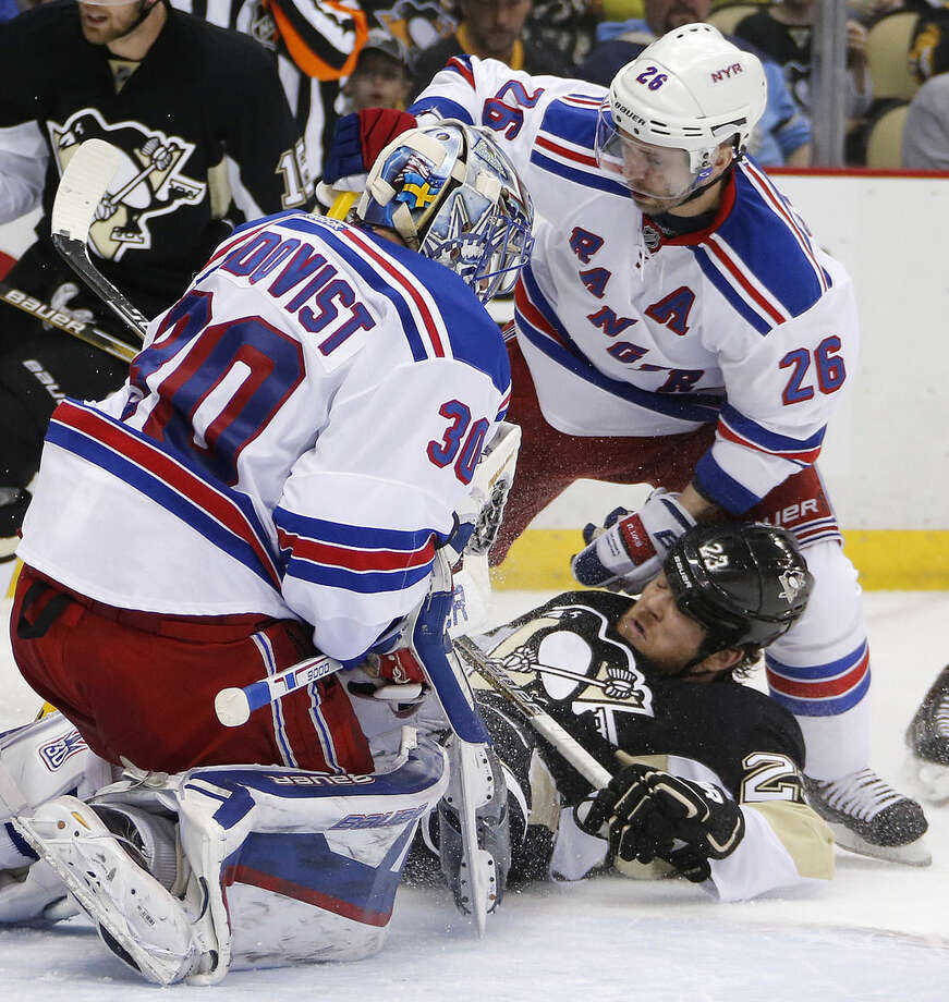 New York Rangers' Martin St. Louis (26) checks Pittsburgh Penguins' Steve Downie (23) to the ice in front of goalie Henrik Lundqvist (30) during the second period of a first-round NHL playoff hockey game in Pittsburgh ib Wednesday, April 22, 2015. (AP Photo/Gene J. Puskar)