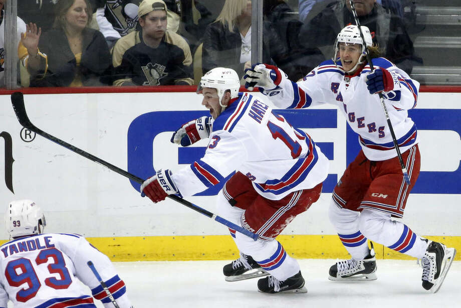 New York Rangers' Kevin Hayes (13) celebrates his game-winning overtime goal with teammate Carl Hagelin (62) during overtime in a first-round NHL playoff hockey game in Pittsburgh on Wednesday, April 22, 2015. The Rangers won 2-1 to take a 3-1 lead in the best-of-seven series. (AP Photo/Gene J. Puskar)