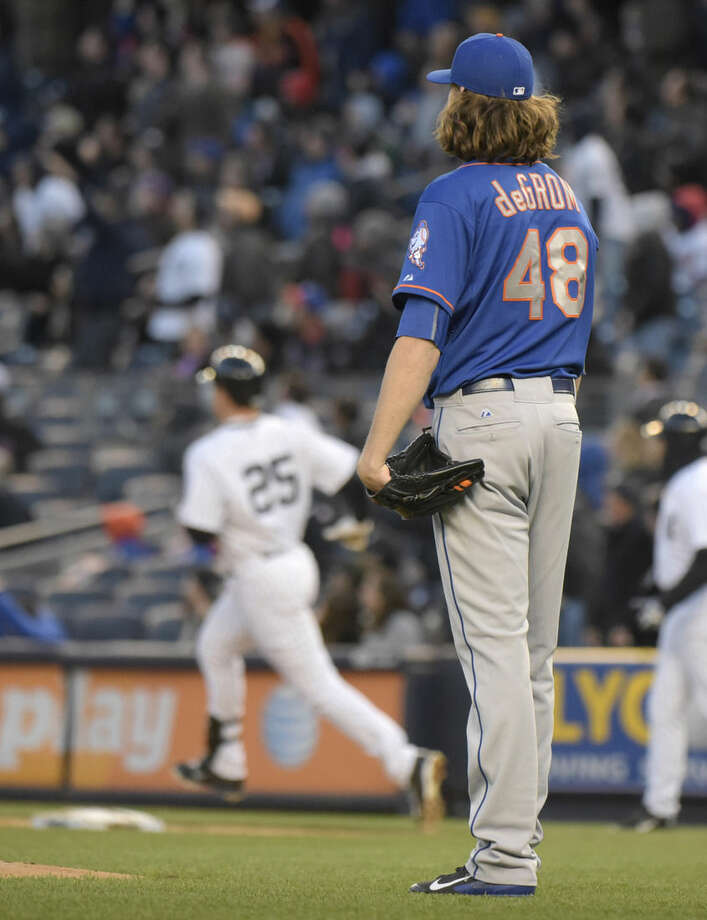 New York Mets pitcher Jacob deGrom (48) watches New York Yankees' Mark Teixeira (25) round the bases after hitting a two-run home run during the first inning of an interleague baseball game Friday, April 24, 2015, at Yankee Stadium in New York. (AP Photo/Bill Kostroun)