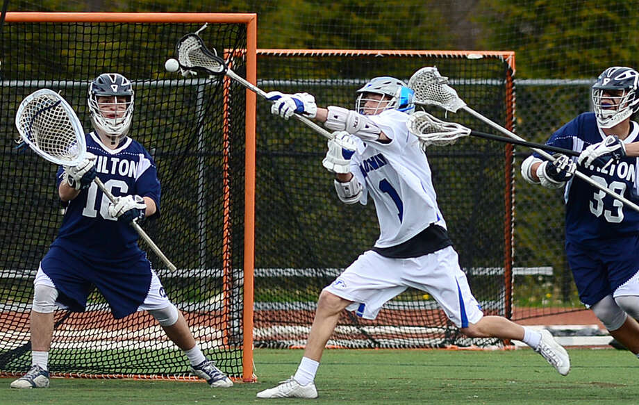 Darien High School's Boys Lacrosse player #1, Brian Minicus takes a shot on Wilton High School's goalie Andrew Calbrese as Wilton's #33 Tyler Previte defends during their game on Saturday, April 22, 2016, at Darien High School in Darien, Conn.