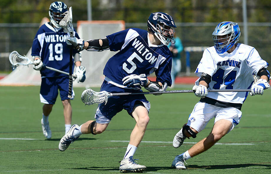 Wilton High School's Boys Lacrosse player #5 Harrison Bardwell tries to get past Darien's #44 Nick Percarpio during their game on Saturday, April 22, 2016, at Darien High School in Darien, Conn.