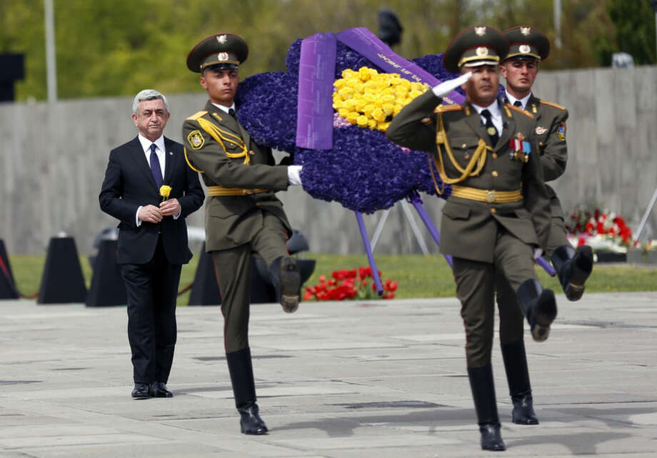 Armenia's President Serge Sarkisian, left, takes part in a wreath laying ceremony during a memorial service at the Tsitsernakaberd Genocide memorial complex in Yerevan, Armenia, Friday, April 24, 2015. On Friday, Armenians mark the centenary of what historians estimate to be the slaughter of up to 1.5 million Armenians by Ottoman Turks, an event widely viewed by scholars as genocide. Turkey, however, denies the deaths constituted genocide and says the death toll has been inflated. (Tigran Mehrabyan/PAN Photo via AP)