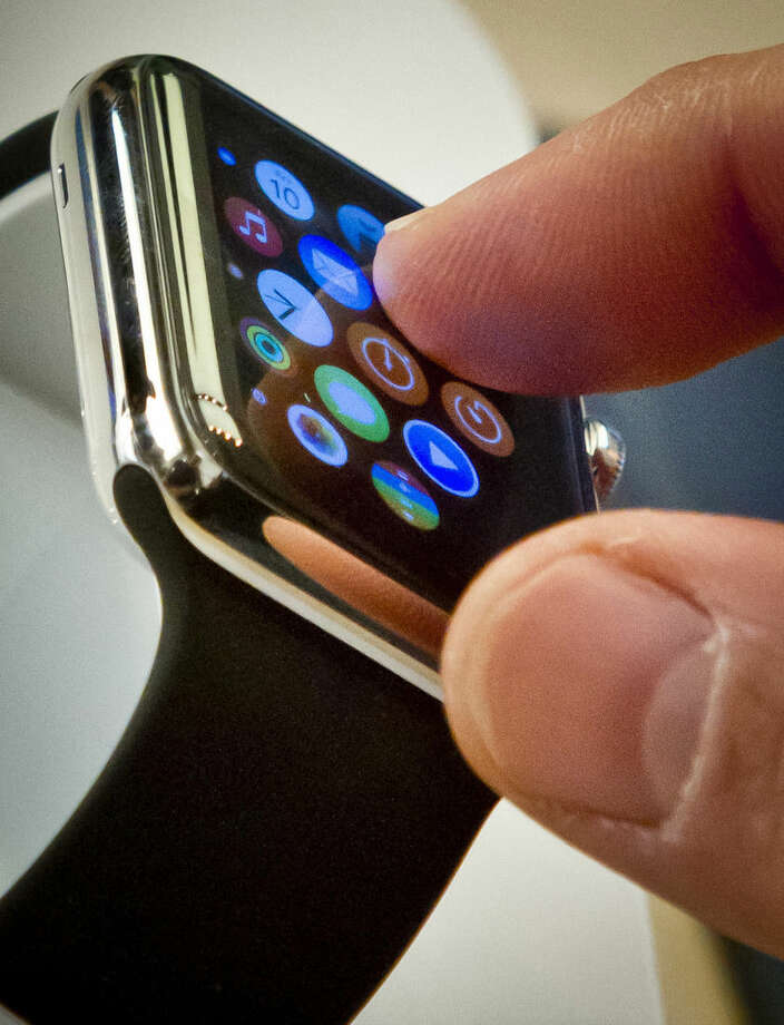 FILE - In this April 10, 2015 file photo, a customer examines Apple's new watch in New York. The first batch of Apple Watches will arrive in people's homes and offices Friday April 24, 2015. (AP Photo/Bebeto Matthews)