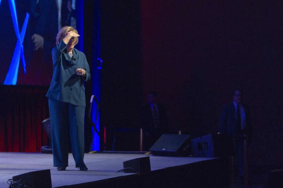 Former U.S. Secretary of State Hillary Rodham Clinton looks into the audience after an object was thrown on stage during her address to members of the Institute of Scrap Recycling Industries during their annual convention at the Mandalay Bay Convention Center, Thursday, April 10, 2014, in Las Vegas. Clinton, a possible presidential contender in 2016, ducked but did not appear to be hit by the object, and then joked about the incident. Security ushered out a woman who said she threw a shoe but didn't identify herself to reporters or explain the action. (AP Photo/Las Vegas Sun, Steve Marcus) LAS VEGAS REVIEW-JOURNAL OUT