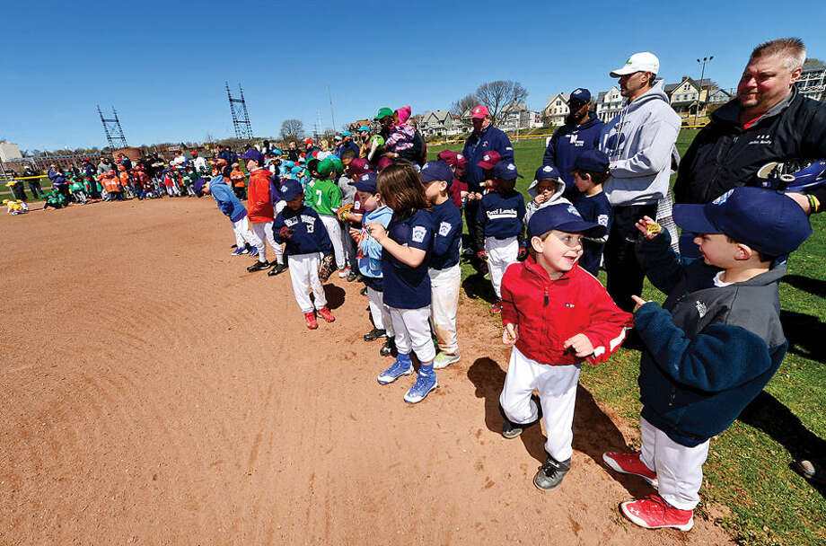 Hour photo / Erik Trautmann Jason Huzina of the Tucci Lumber Little leagur team, second from rifght, is excited to play during the Norwalk Little League opening day ceremonies Saturday at Veteran's Park.